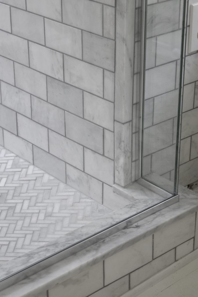 corner shower view carrara marble subway and herringbone tile