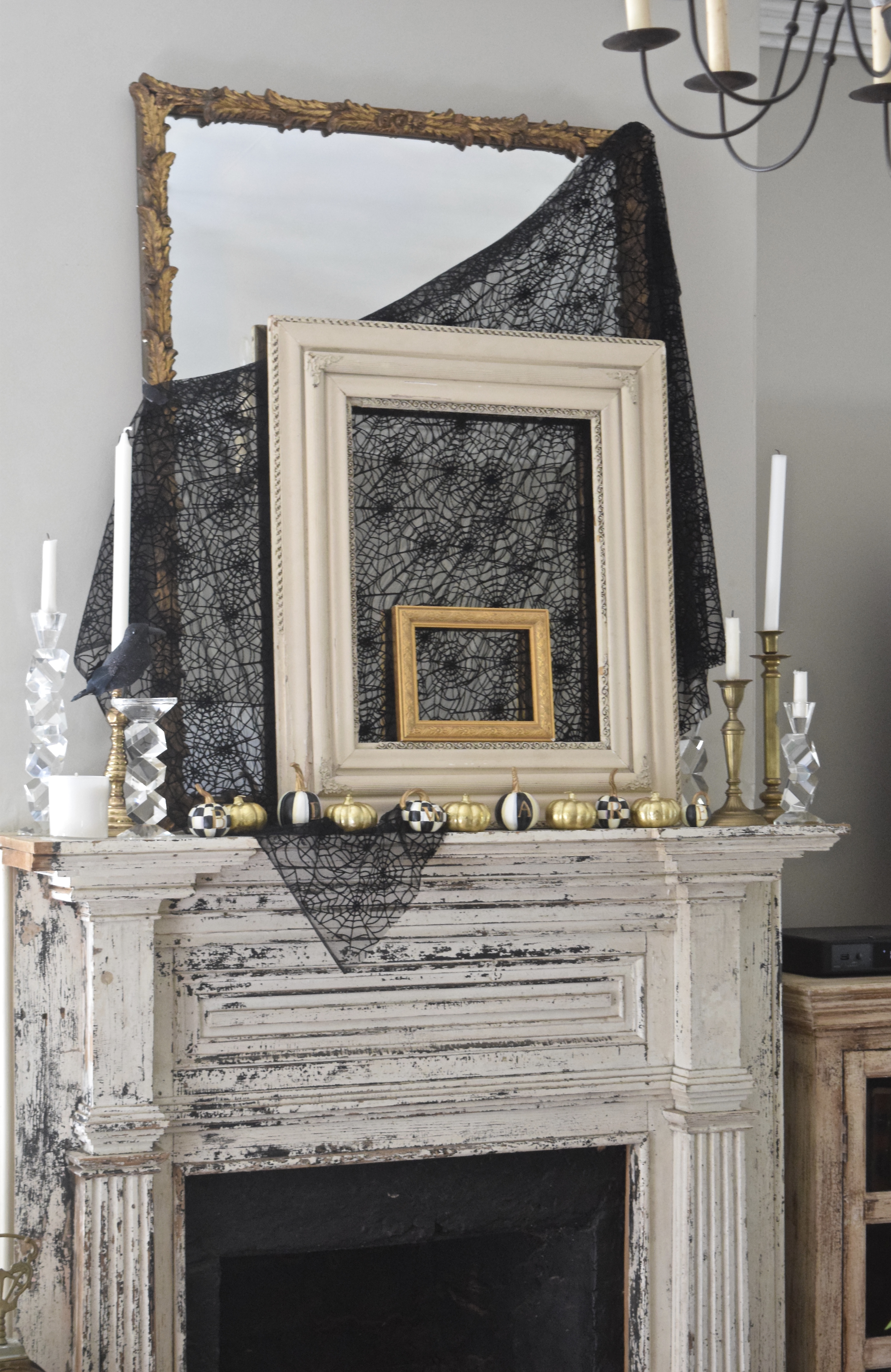 glam halloween mantel with layered pictures frames