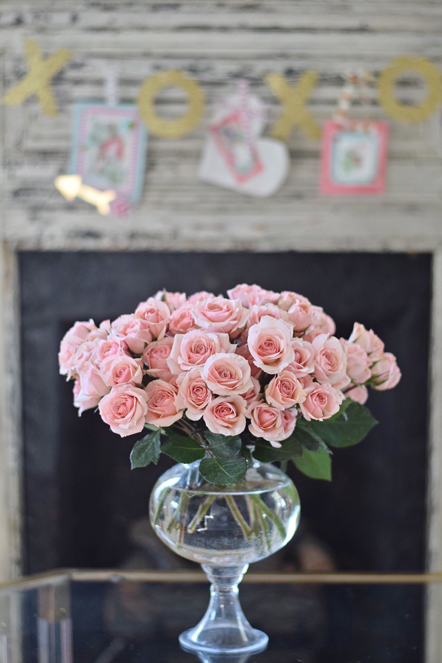 pink roses in front of valentines day mantel